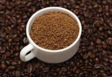 Café solúvel em xícara com grãos de café ao redor